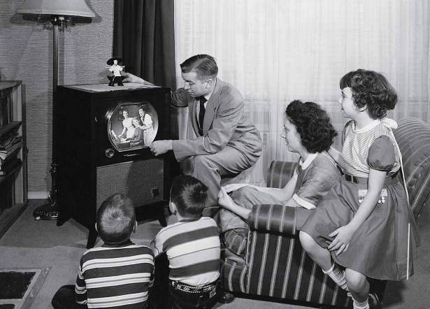 parents-with-three-children-watching-television