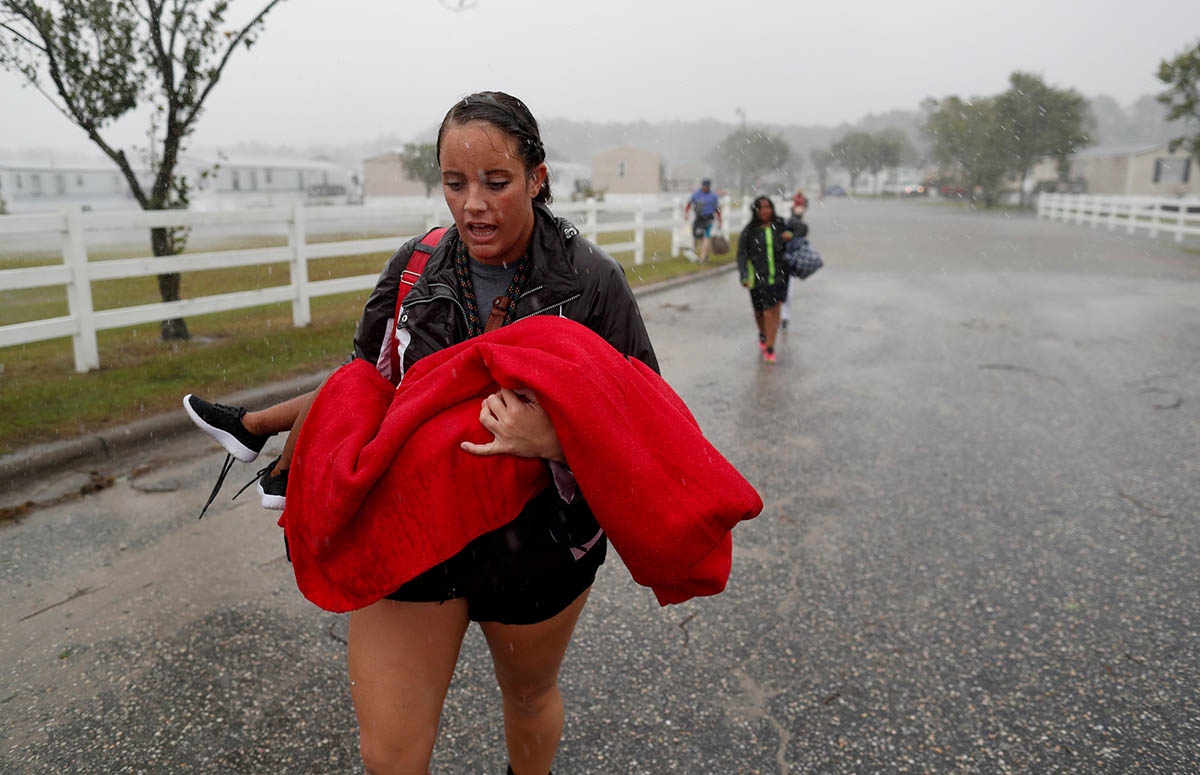 During a driving rain, Maggie Belgie of The Cajun Navy, carries a child evacuating a flooding trailer community during Hurricane Florence in Lumberton